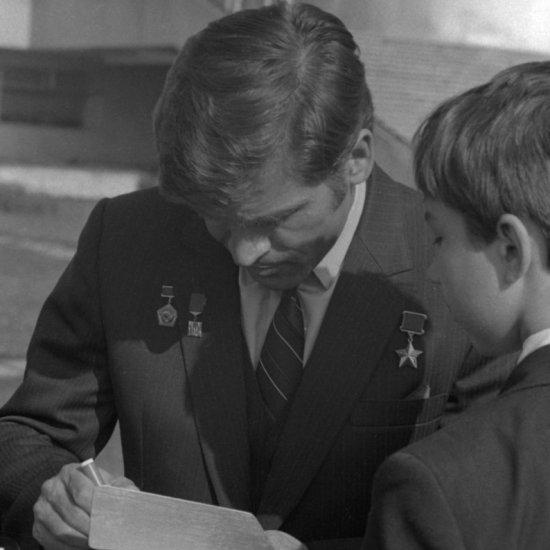 Летчик-космонавт СССР А.А. Серебров дает автограф юному ракетомоделисту.