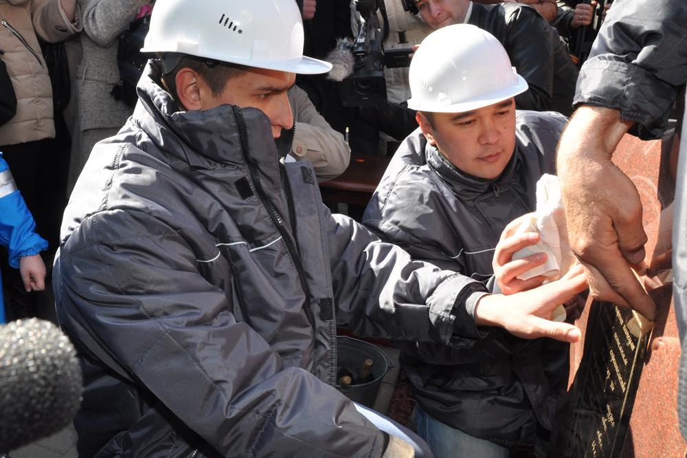 Представитель подрядчика крепят памятную табличку