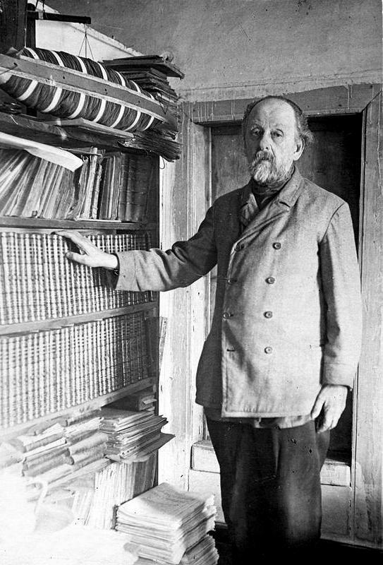 К.Э. Циолковский в рабочем кабинете у полки с книгами.